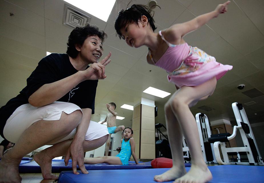 बीजिंग के एक ट्रेनिंग सेंटर में डाइविंग ट्रेनिंग सेशन से पहले बैलेंसिंग प्रैक्टिस करती हुई 5 साल की बच्ची.(image credit: Reuters)