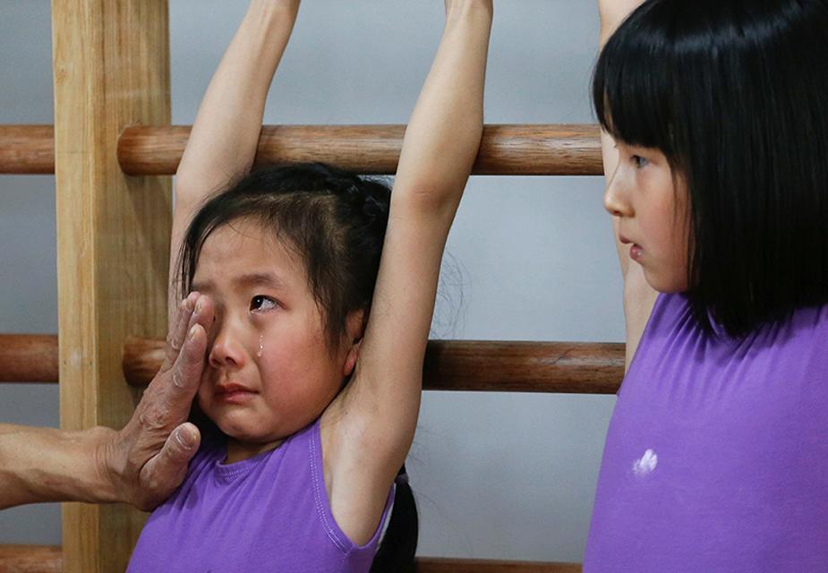 जिमनास्टिक की ट्रेनिंग के दौरान एक कोच छोटी सी बच्ची के आंसू पोछते और दिलासा देते देखे जा सकते हैं.(image credit: Reuters)