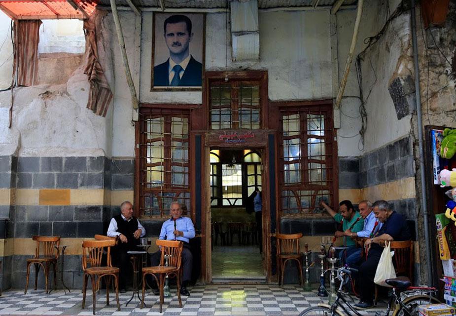 सीरिया के दमिश्क शहर की ये तस्वीर है. यहां के हमिदिया मार्केट में स्थित एक कॉफी शॉप में हुक्का पीते लोगों को आप देख सकते हैं. दुकान के ऊपर बशर अल-असद की तस्वीर भी टंगी हुई है.(image credit: AP)