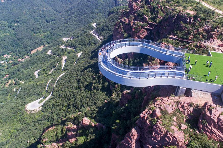 चीन के हेनान में फूक्सी पहाड़ पर बना ये है दुनिया का सबसे लंबा शीशे का यू-आकार का ब्रिज. (image credit: Getty)