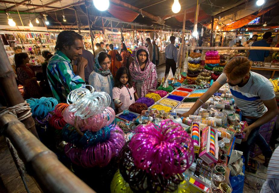 पाकिस्तान के इस्लामाबाद में एक परिवार पारंपरिक चूढ़ियां खरीदते देखे जा सकते हैं.(image credit: AP)