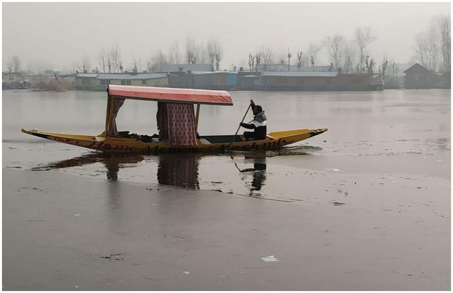 बर्फ़बारी के कारण जम चुकी झील में शिकार चलाने की जुगत में शिकारे वाला.