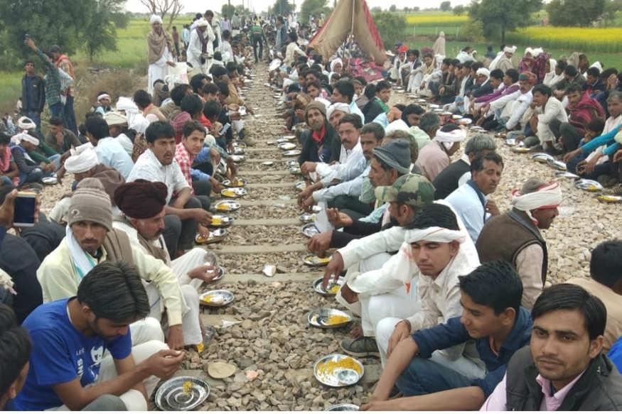 आंदोलन की मांग को लेकर गुर्जर समाज के लोग गुर्जर आरक्षण संघर्ष समिति के नेतृत्व में दिल्ली-मुंबई रेलवे-ट्रैक पर कब्जा किए बैठे हैं. सुबह-शाम पटरियों पर पंक्तिबद्ध रूप से बैठकर सामूहिक रूप से भोजन किया जाता है.