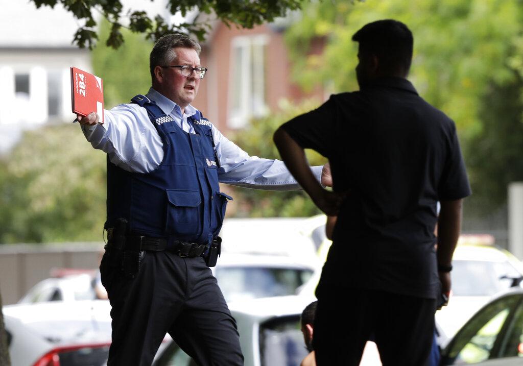 सेंट्रल क्राइस्टचर्च में मस्जिद के बाहर लोगों को हटाता हुआ पुलिस जवान (स्रोतःएपी)
