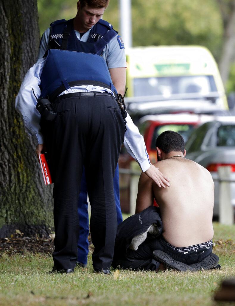 सेंट्रल क्राइस्टचर्च में एक आदमी को दिलासा देती हुई पुलिस. गोलीबारी की घटना में 27 लोगों के मारे जाने की खबर है.