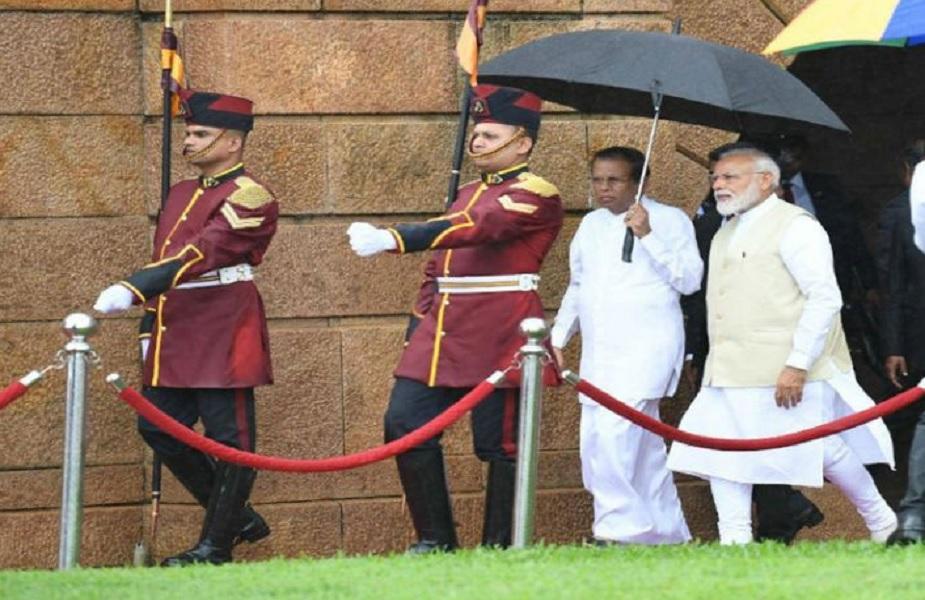 राजधानी कोलंबो में पीएम मोदी अगवानी में राष्ट्रपति सिरिसेना ने अन्य अधिकारियों की बजाय खुद ही छाता संभाल लिया और उनके साथ छाता तान कर चले.