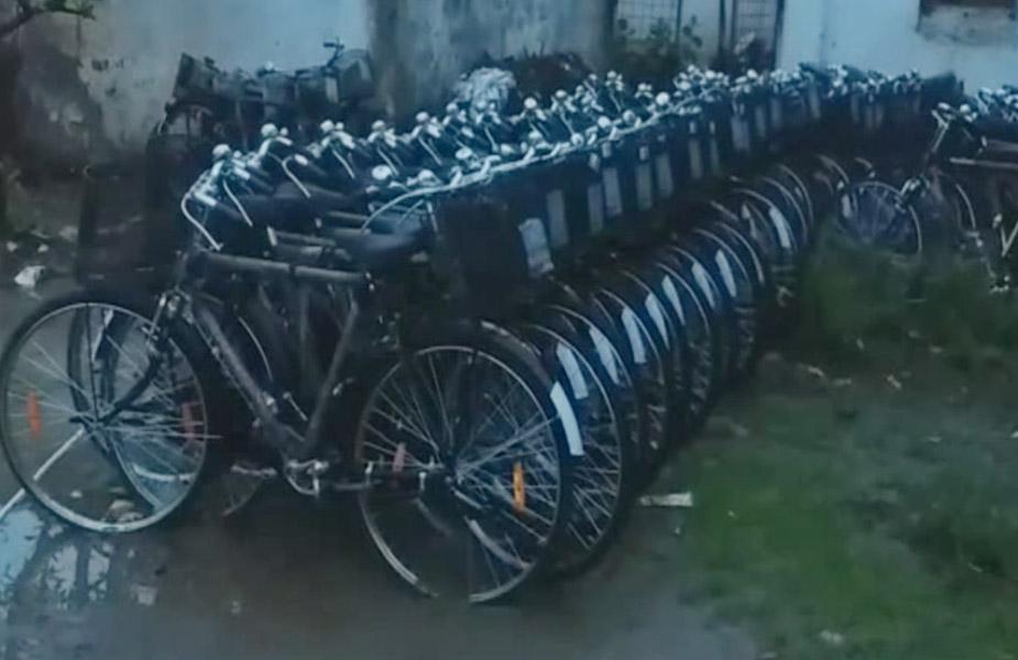 जो साइकिलें अबतक बच्चों के पास होनी चाहिए थीं, वो खुले आसमान के नीचे धूल-धूप और बारिश में पड़ी हुई हैं.