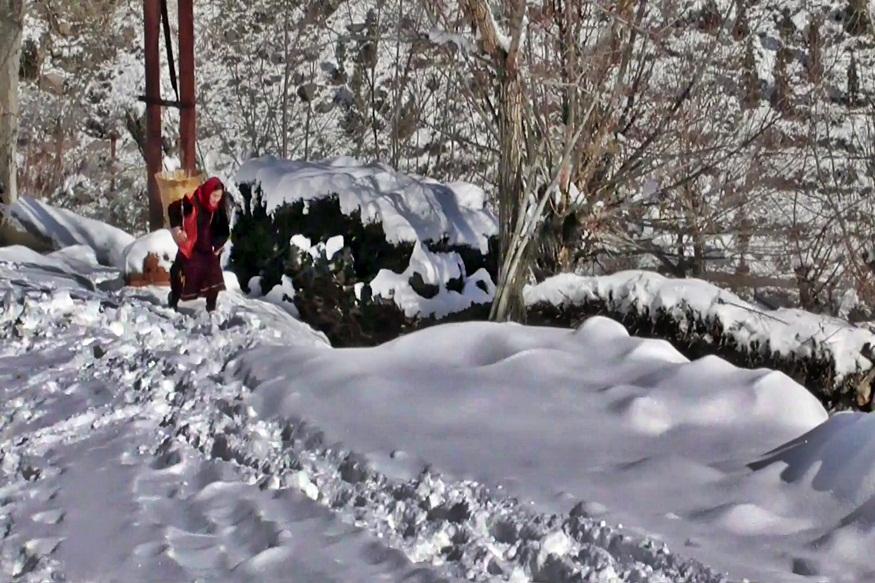 केलांग में बर्फ से गुजरती महिला.