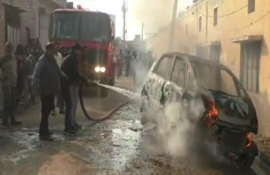 दमकल विभाग के कर्मचारी कार में लगी आग को बुझाते हुए
