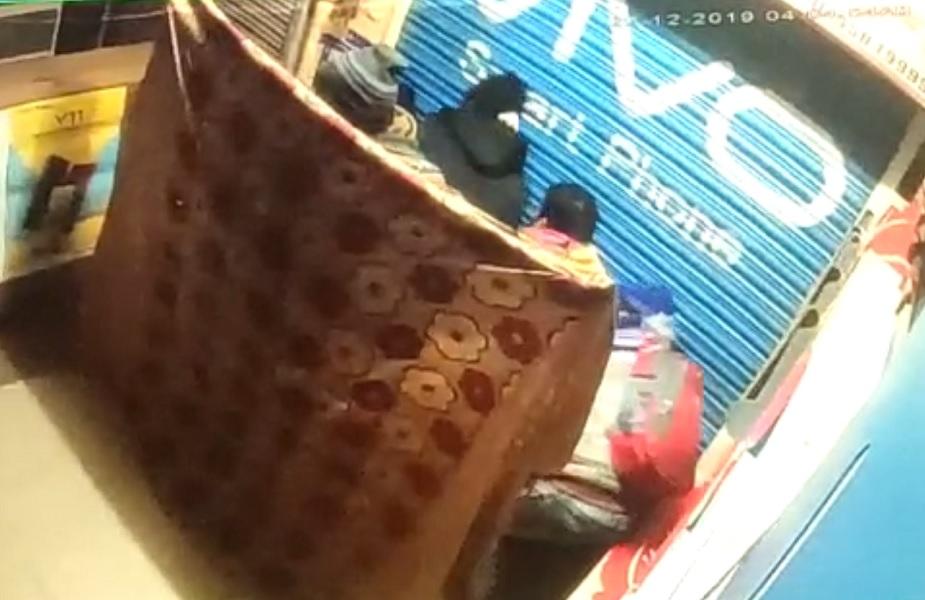 शटर तोड़ने के लिए चादर से साथियों को ढकता चोर